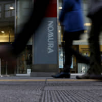 edestrians walk past a signboard of Nomura Securities outside its branch in Tokyo in 2016. | REUTERS