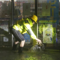 A convenience store owner tries to block water from flooding his store in Tokyo's Setagaya Ward on Saturday evening as Typhoon Hagibis passes through the Kanto region. | KYODO