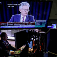 Traders work as a screen shows footage of U.S. Federal Reserve Chairman Jerome Powell's news conference after the Fed's interest rate announcement on the floor of the New York Stock Exchange on Wednesday. | REUTERS