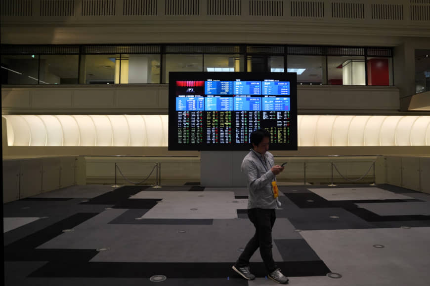 A man walks in front of a screen displaying share prices inside the Tokyo Stock Exchange in May. | BLOOMBERG