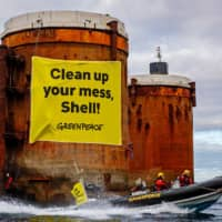 Greenpeace activists climb Shell North Sea platforms and hang 'clean up your mess' sign