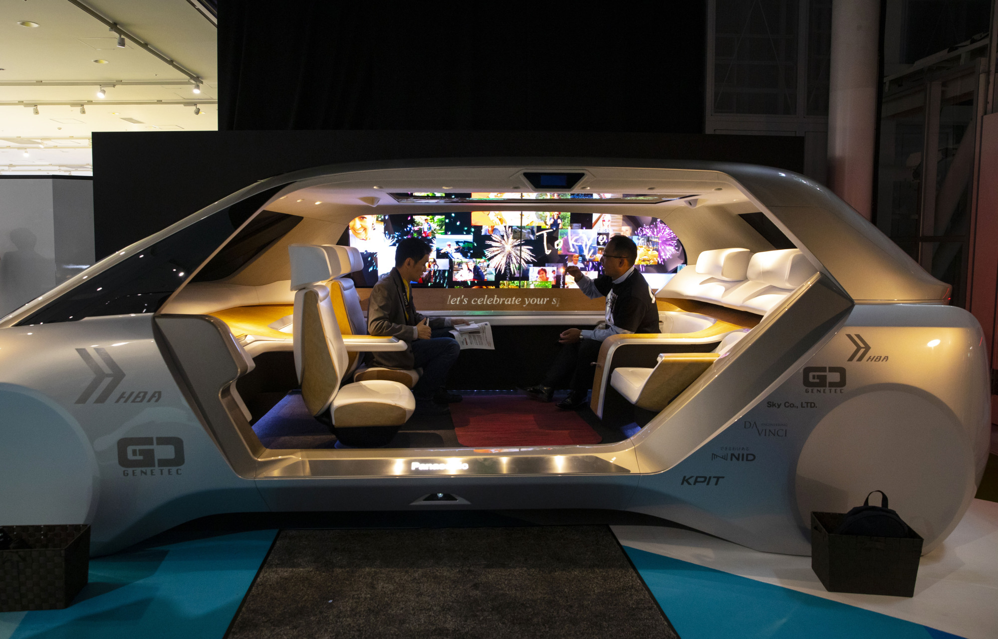 People sit in a Panasonic Corp. Autonomous Living Space Cabin concept vehicle on display at the Tokyo Motor Show in Tokyo on Oct. 23. | BLOOMBERG