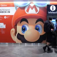 A big ad directs travelers to a Nintendo Co. pop-up event at the Visitor Service Center in Narita International Airport in August. | BLOOMBERG