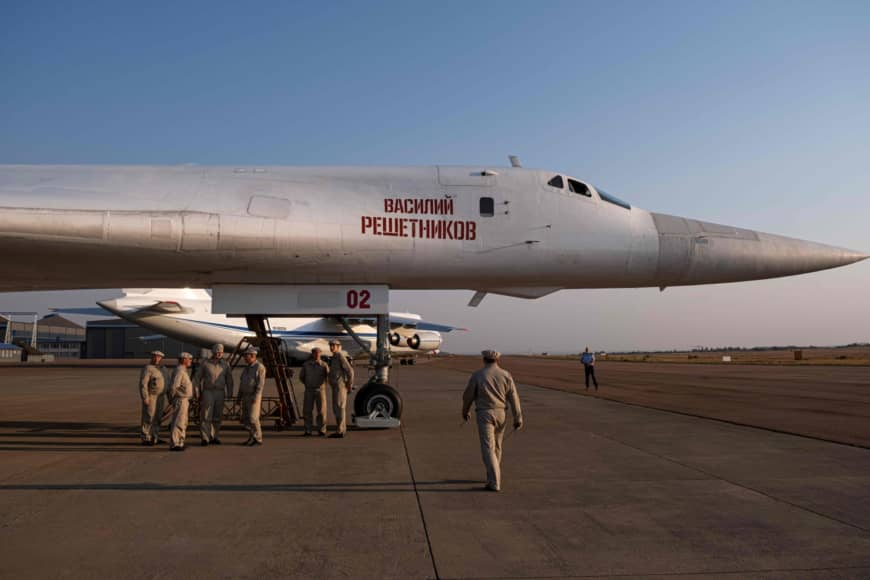 Military personnel gather under a Russian Air Force Tupolev Tu-160