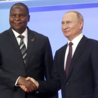 Russian President Vladimir Putin (right) and President of the Central African Republic Faustin Archange Touadera pose for a photo during a welcome ceremony of the Russia-Africa summit in the Black Sea resort of Sochi, Russia, Wednesday. | SERGEI CHIRIKOV / POOL PHOTO / VIA AP