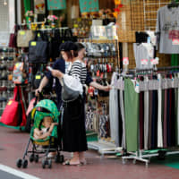 Shoppers look at goods in Tokyo on Oct. 1. Although Japan's retail sales rose the highest in more than five years, some experts worry that the October tax hike might drag down spending in the coming months. | REUTERS