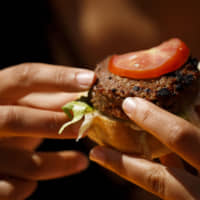 SoftBank Group Corp. is eyeing investments in a burger startup and a pharmaceutical delivery firm. | BLOOMBERG