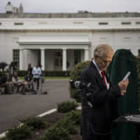 Peter Navarro, director of the National Trade Council, prepares for a television interview outside of the White House in Washington on Tuesday. The U.S. blacklisting surveillance company Hikvision is unrelated to U.S.-China trade talks in Washington this week, Navarro said. | BLOOMBERG