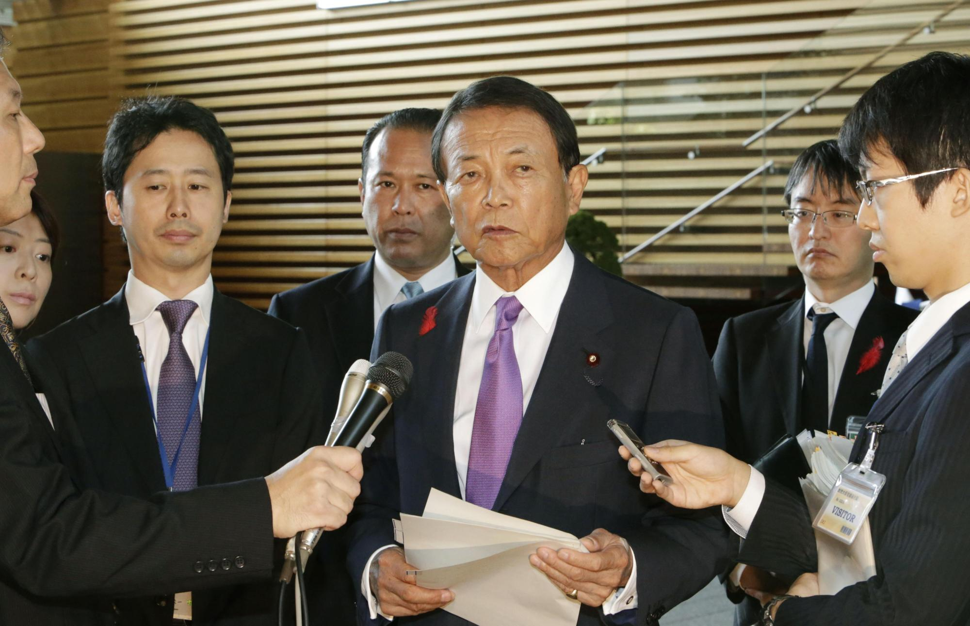 Finance Minister Taro Aso speaks to reporters on Tuesday at the Prime Minister's Office in Tokyo. Japan hiked its consumption tax to 10 percent from 8 percent on the same day.   KYODO