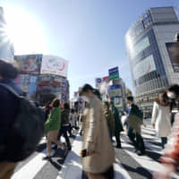 People cross an intersection in Tokyo's Shibuya district in March. | BLOOMBERG