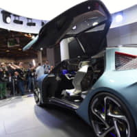 Media crews gawk at Toyota Motor Corp.'s Lexus LF-30 electric concept vehicle during the 46th Tokyo Motor Show's media day Wednesday in the Odaiba district. | BLOOMBERG