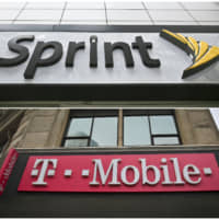 This  2018 photo combo shows signage for a Sprint store in New York's Herald Square and signage at a T-Mobile store in New York. T-Mobile says it expects its combination with Sprint to close next year as it awaits a December antitrust trial with a group of state attorneys general. | AP