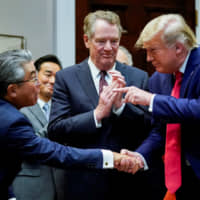 U.S. President Donald Trump shakes hands with Japanese Ambassador to the United States Shinsuke Sugiyama in front of U.S. Trade Representative Robert Lighthizer during a formal signing ceremony for the U.S.-Japan trade agreement at the White House in Washington on Oct. 7. | REUTERS