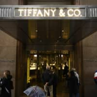 People walk past the headquarters of luxury jewelry and specialty retailer Tiffany & Co on 5th Avenue in Manhattan on Sunday in New York City. LVMH, the French owner of Louis Vuitton, is exploring a takeover of Tiffany & Co to expand in the U.S. jewelry market, according to reports. | AFP-JIJI