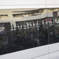 Relatives and journalists are reflected against the tinted windows of a police van taking Hajar Rissouni away from a court after she was sentenced to one year in prison on accusations of her undergoing an illegal abortion, in Rabat Monday.   AP