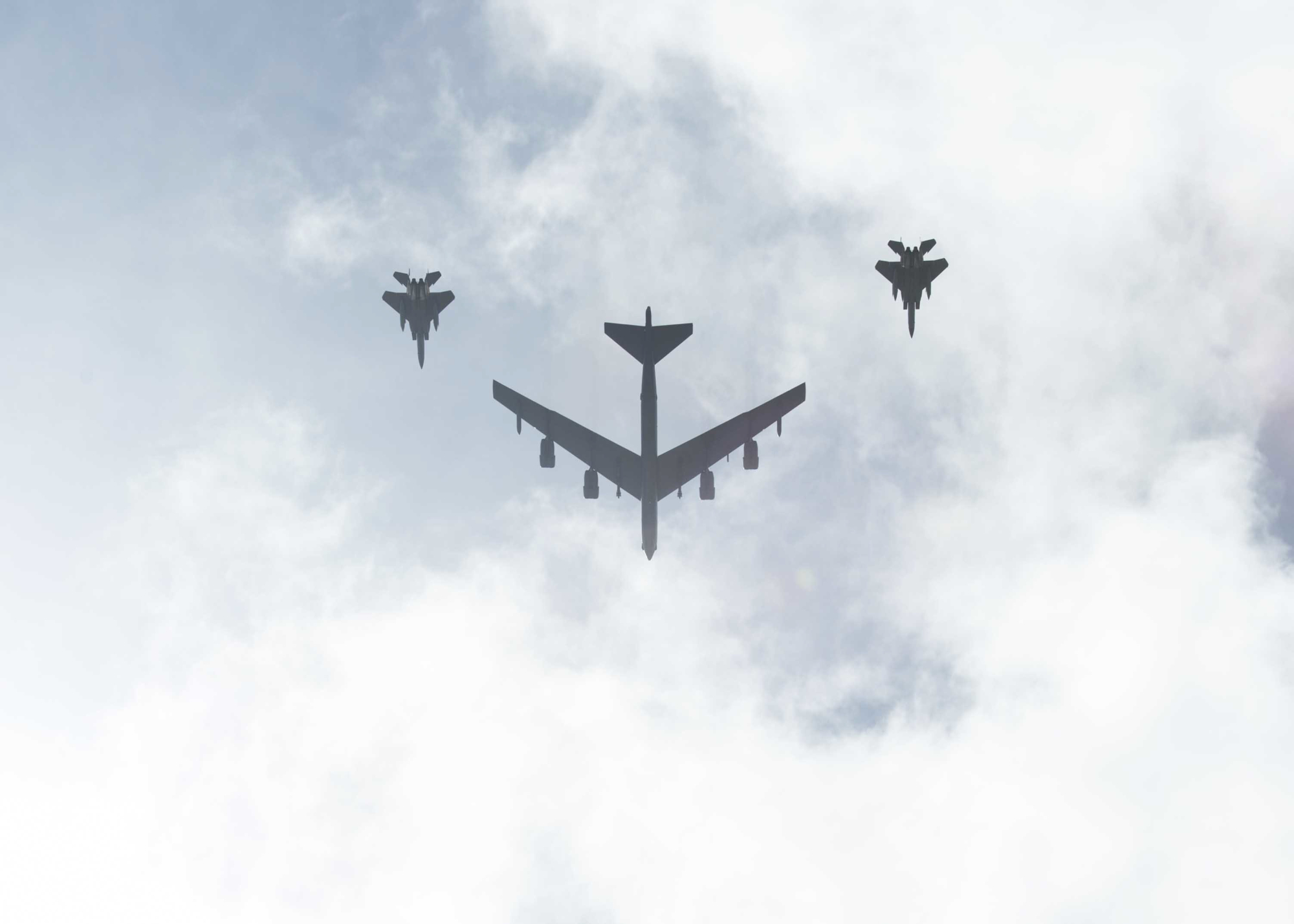 A B-52 bomber, escorted by F-15E Strike Eagle tactical ground attack aircraft, flies over the 75th Guam Liberation Day parade on July 21 in Hagatna, Guam. | U.S. NAVY