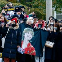 Fans of G-Dragon wait outside an army base in Yongin on Saturday.   REUTERS