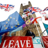 An anti-Brexit protester waves an EU flag outside the Houses of Parliament in London Friday.   REUTERS