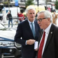 President of the European Commission Jean-Claude Juncker (right) and EU chief Brexit negotiator Michel Barnier arrive for a European Union summit at the European Union headquarters in Brussels on Thursday. | AFP-JIJI
