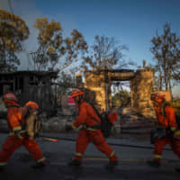 Inmate firefighters walk past a burnt home during the Getty Fire in Brentwood, California, on Monday. | AFP-JIJI