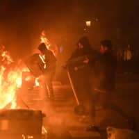 Protesters burn garbage containers during protests in Barcelona, Spain, on Tuesday. | AFP-JIJI