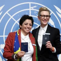 UNHCR goodwill ambassador and actress Cate Blanchett and formerly stateless refugee Maha Mamo (left) pose with passports after a news conference during a High-Level Segment on Statelessness, part of the UNHCR's Executive Committee meeting, at the United Nations in Geneva Monday. | REUTERS