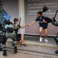Hong Kong police chase down a couple wearing face masks in Hong Kong on Saturday, a day after the city's leader outlawed face coverings at protests invoking colonial-era emergency powers not used for half a century. | AFP-JIJI