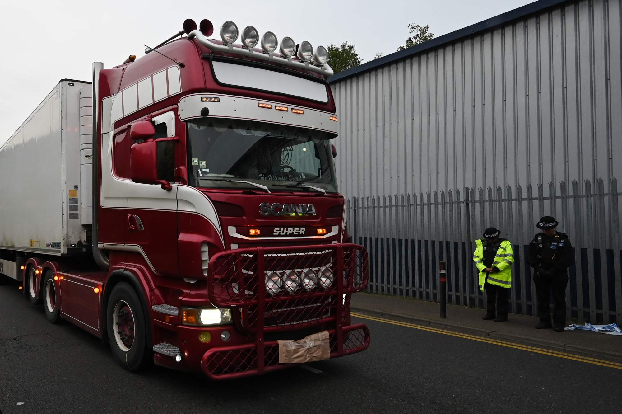 Police officers drive away a truck in which 39 dead bodies were discovered sparking a murder investigation at Waterglade Industrial Park in Grays, east of London, on Wednesday. | AFP-JIJI