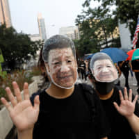 Anti-government demonstrators wear masks bearing the image of Chinese President Xi Jinping during a protest against the invocation of the emergency laws in Hong Kong on Oct. 12. | REUTERS