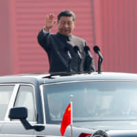 Chinese President Xi Jinping waves from a vehicle as he reviews the troops at a military parade marking the 70th founding anniversary of the People's Republic of China on Oct. 1. | REUTERS