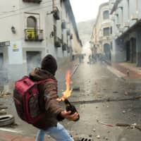 A demonstrator prepares to throw a Molotov cocktail at the police following the announcement of a transport strike against the economic policies of the government of Ecuadorean President Lenin Moreno regarding the agreement signed on March with the International Monetary Fund (IMF), in Quito Thursday. | AFP-JIJI