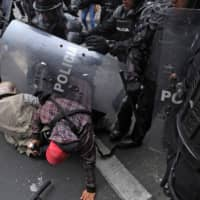 Journalists of the El Comercio newspaper are attacked by police during a protest following the announcement of a transport strike against Ecuadorean President Lenin Moreno's government economic policies regarding the agreement signed last March with the International Monetary Fund (IMF) in downtown Quito on Thursday. | AFP-JIJI