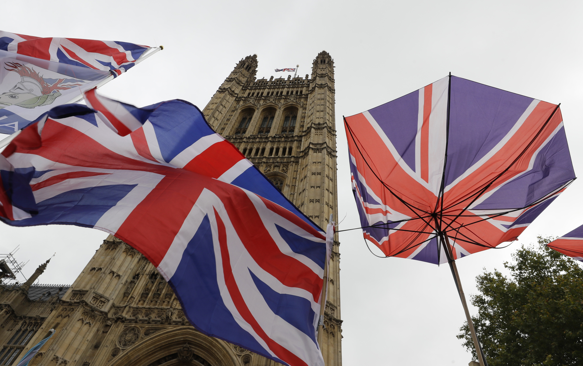 Union flags and an umbrella tied to railings are seen in front of Parliament in London on Friday. | AP