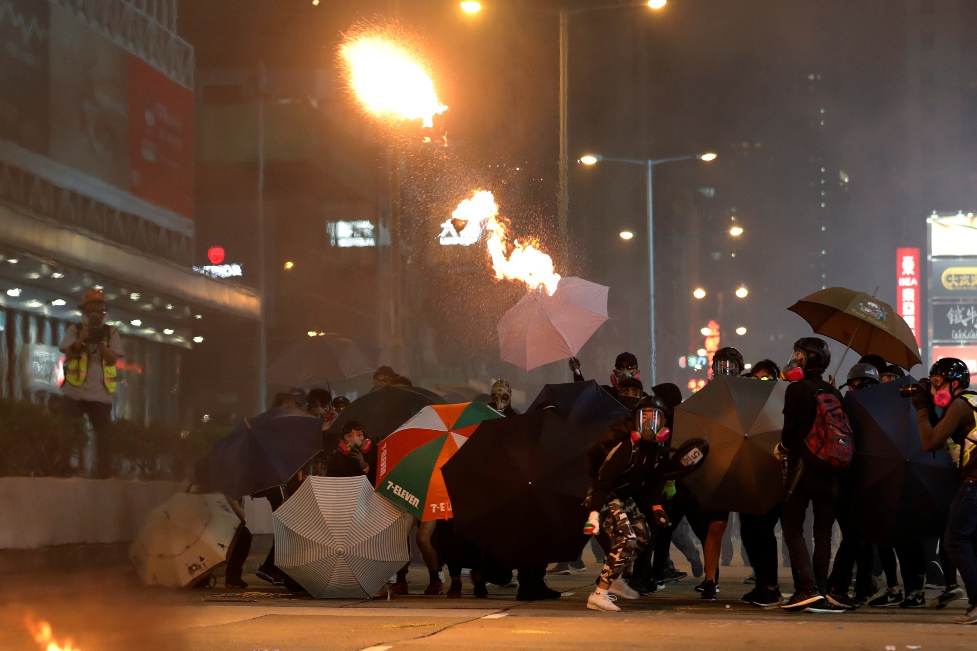 An anti-government protester throws a petrol bomb during a protest in Hong Kong's tourism district of Tsim Sha Tsui, on Wednesday. | REUTERS