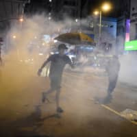Protesters react after police fired tear gas in the Mong Kok district in Hong Kong on Monday. | AFP-JIJI