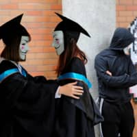 University students wearing Guy Fawkes masks pose for a photo to support anti-government protests at the Hong Kong Polytechnic University on Wednesday. | REUTERS