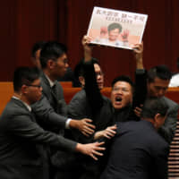 A pro-democracy lawmaker is removed from the Legislative Council as Hong Kong Chief Executive Carrie Lam speaks on Thursday. | REUTERS