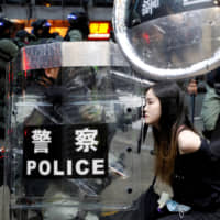 Riot police detain a protester during an anti-government rally in central Hong Kong on Sunday. | REUTERS