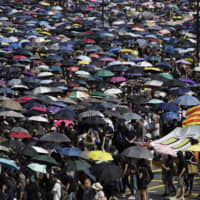Protesters hold umbrellas and a Catalonia independence flag as they march in Hong Kong on Sunday. Protesters again flooded streets, ignoring a police ban on the rally and demanding the government meet their demands for accountability and political rights. | AP