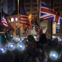 Protesters hold up their smartphone near British and American flags during a prayer rally at Edinburgh Place in Hong Kong late Saturday. | AP