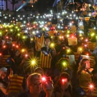 People hold Catalan pro-independence Estelada flags and light up their mobile phones during a Hong Kong-Catalonia solidarity assembly in the city's Central district on Thursday. | AFP-JIJI