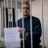 Paul Whelan, a former U.S. Marine accused of espionage and arrested in Russia in December 2018, holds a message as he stands inside a defendants' cage before a hearing to decide to extend his detention at the Lefortovo Court in Moscow on Thursday. | AFP-JIJI