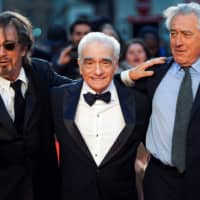 Director Martin Scorsese and flanking cast members Al Pacino (left) and Robert De Niro arrive for the screening of 'The Irishman' during the 2019 BFI London Film Festival at the Odeon Luxe Leicester Square in London Sunday. | REUTERS