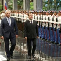 Cuban President Miguel Diaz-Canel and Russian Prime Minister Dmitry Medvedev (right) review an honor guard during a ceremony at the Revolution Palace in Havana Thursday. | REUTERS