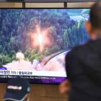 People watch file footage of a North Korean missile launch on a TV screen at a railway station in Seoul on Thursday. | AFP-JIJI