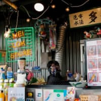 A storekeeper wears a gas mask while selling drinks to protesters as riot police fire tear gas at Tsim Sha Tsui in Hong Kong on Sunday. | REUTERS