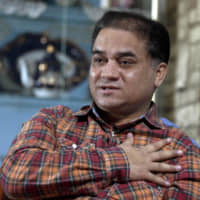 Scholar Ilham Tohti gives an interview at his home in Beijing in February 2013. | AP