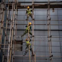 Workers erect scaffolding at a construction site in Beijing on Saturday. | AFP-JIJI