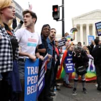 LGBTQ activists and supporters block the street outside the U.S. Supreme Court as it hears arguments in a major LGBT rights case on whether a federal anti-discrimination law that prohibits workplace discrimination on the basis of sex covers gay and transgender employees, in Washington Tuesday. | REUTERS