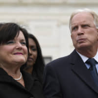 R.G. & G.R. Harris Funeral Homes owner Thomas Rost and his wife, Nancy Rost, listen during a news conference outside the Supreme Court in Washington Tuesday. Aimee Stephens, who was employed at the Detroit-area R.G. and G.R. Harris Funeral Homes, lost her job after telling Thomas Rost that she had struggled with gender identity issues almost her whole life. Their case was argued before the Supreme Court earlier in the day. | AP